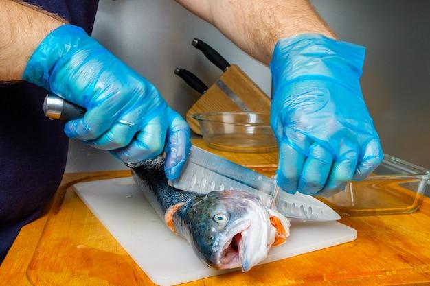 Ręce kucharza w higienicznych rękawiczkach odcinają nożem głowę łososia.
