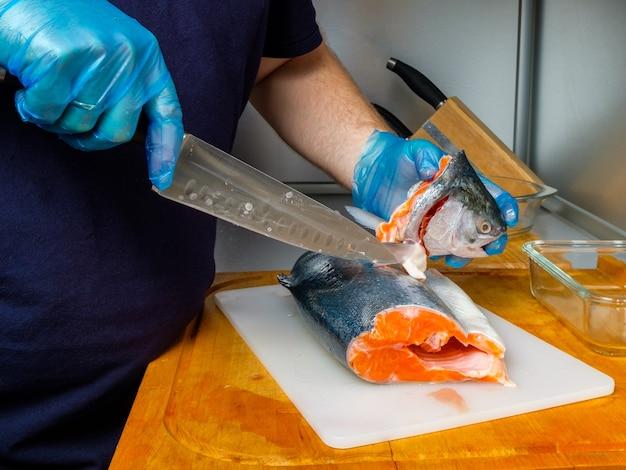 Ręce kucharza w rękawiczkach odcinają nożem głowę łososia