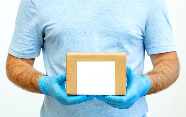 Ręce kuriera w gumowych rękawiczkach medycznych trzymających kartony. dostawa do drzwi.