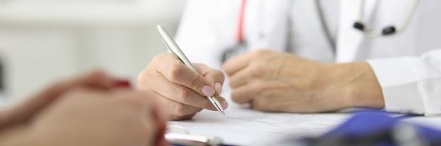 Ręce lekarza i pacjenta na stole roboczym w gabinecie lekarskim