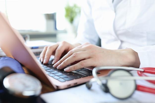 Ręce lekarza pracującego na laptopie leżą obok stetoskopu. koncepcja usług terapeuty