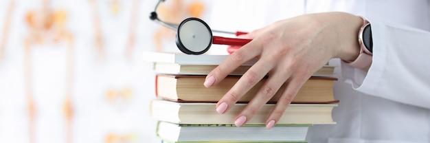 Ręce lekarza trzymają stos książek i stetoskop