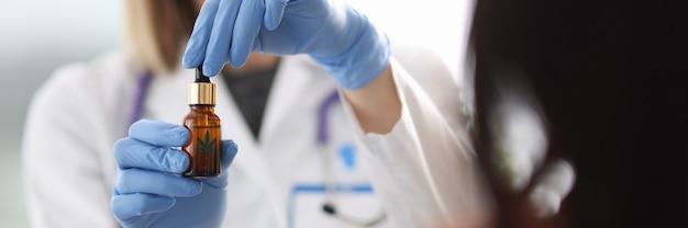 Ręce lekarza trzymają szklaną butelkę marihuany. leczenie marihuaną dla pacjentów z koncepcją zaburzeń układu nerwowego