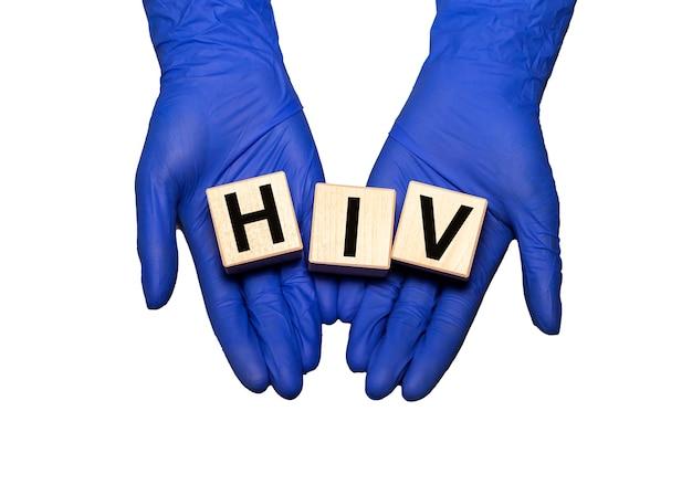 Ręce lekarza w rękawice medyczne trzymać drewniane klocki kostki z akronimem hiv ludzkiego wirusa niedoboru odporności na białym tle na białej powierzchni.