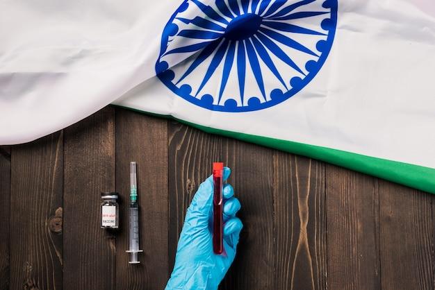 Ręce lekarza w rękawiczkach trzymających koronawirusa do prób krwi