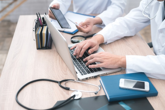 Ręce lekarzy, którzy siedzą przed komputerem.