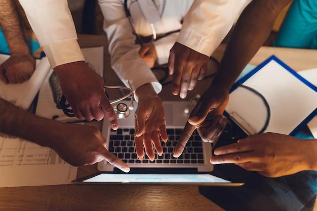 Ręce lekarzy różnych ras pokazują na laptopie.