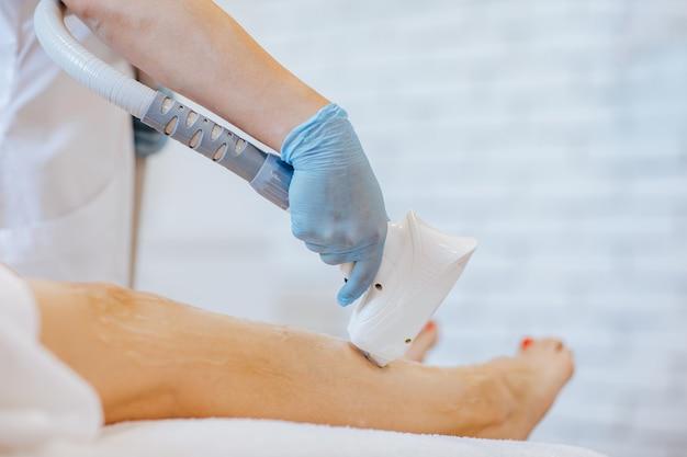Ręce lekarzy w niebieskich rękawiczkach medycznych trzymających maszynę do depilacji i używających jej na nogach kobiety.