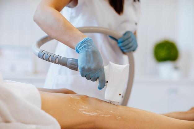 Ręce lekarzy w niebieskich rękawiczkach medycznych trzymających maszynę do depilacji i używających jej na nogach kobiety