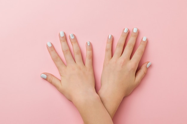 Ręce leżące jedna na drugiej ze stylowym makijażem na różowej powierzchni