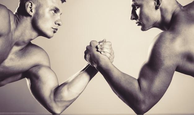 Ręce lub ramiona człowieka. muskularna ręka. mocowanie się na rękę. rywalizacja, zbliżenie męskich siłowania się na rękę. dwie ręce. muskularni mężczyźni mierzą siły, ramiona. zapasy ręczne, rywalizuj. czarny i biały.