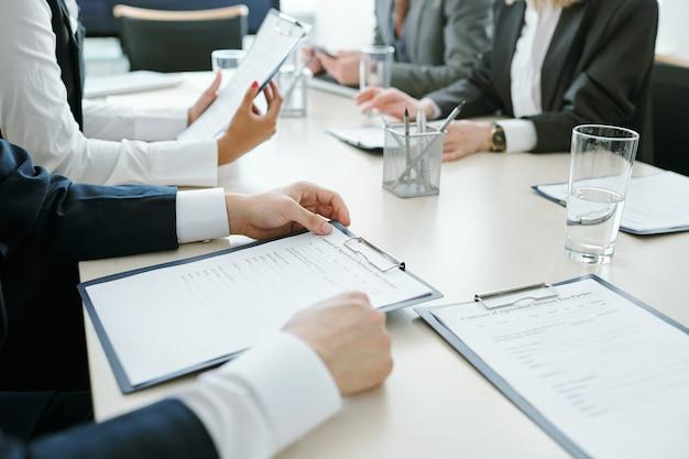 Ręce ludzi biznesu w formalnej odzieży siedzącej przy biurku naprzeciwko siebie i czytając dokumenty podczas przygotowań do konferencji