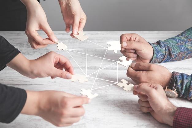 Ręce ludzi trzymających puzzle. połączenie, partnerstwo, sukces, praca zespołowa