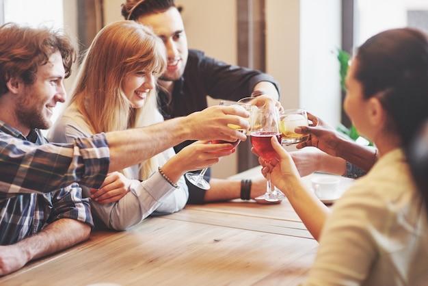 Ręce ludzi w szklankach whisky lub wina, świętujących i opiekających