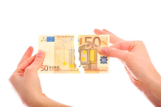 Ręce łzawiące banknot pięćdziesiąt euro na białym tle
