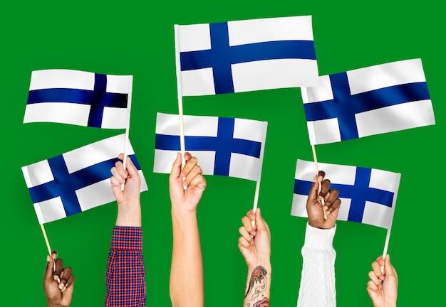 Ręce macha flagami finlandii