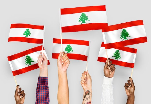 Ręce macha flagami libanu