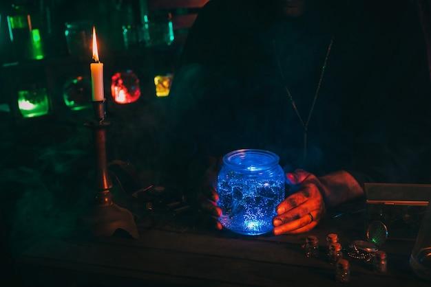 Ręce magika alchemika naukowca z kolbą z magiczną miksturą przy stole w mistycznym laboratorium