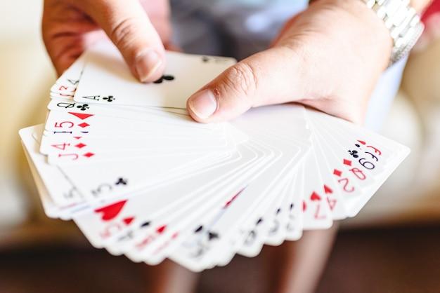 Ręce magika robi magiczną sztuczkę z kart do gry.