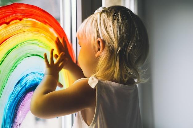 Ręce małej dziewczynki dotykają malowania tęczy na oknie sztuka dziecięca i kreatywna!