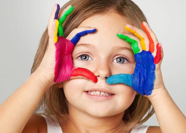 Ręce małej dziewczynki i chłopca pomalowane kolorowymi farbami