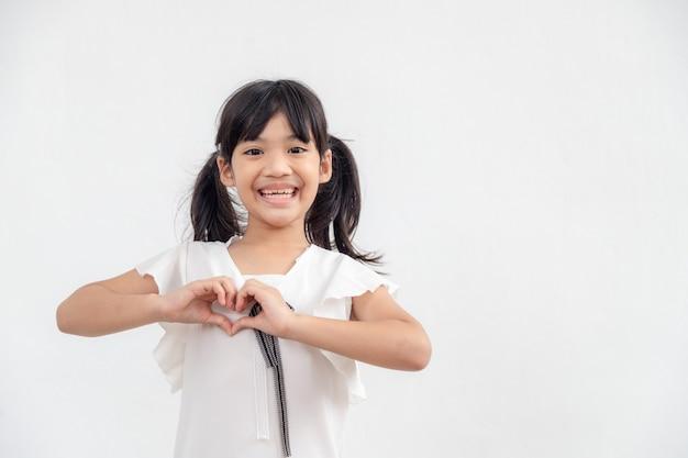 Ręce małej dziewczynki tworzące kształt serca na białym tle