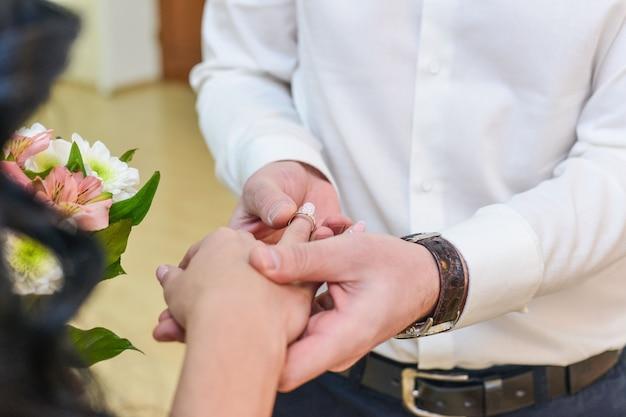 Ręce małżeństwa z pierścieniami. birde nosi pierścień na palcu pana młodego