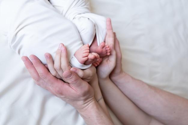 Ręce mamy i taty trzymają małe nóżki ich dwojga noworodków bliźniaków.