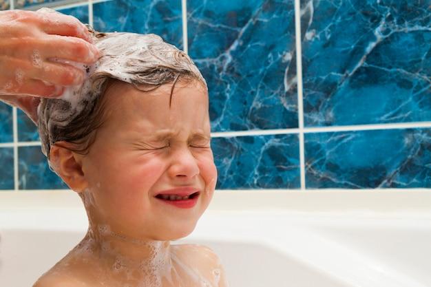Ręce mamy myją głowę małej dziewczynki w łazience. symbol edukacji czystości i higieny.