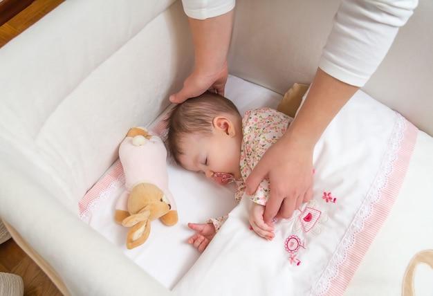 Ręce mamy pieszczące swoją śliczną córeczkę śpiącą w łóżeczku ze smoczkiem i pluszową zabawką