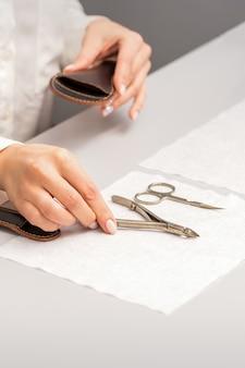 Ręce manikiurzystki odkładają na stole narzędzia do manicure, przygotowując się do zabiegów manicure