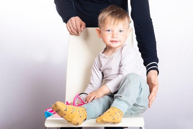 Ręce matki chronią chłopca siedzącego na krześle na jasnej powierzchni