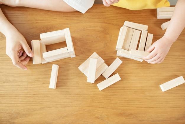 Ręce matki i córki, budowanie wież z drewnianych cegieł, widok z góry