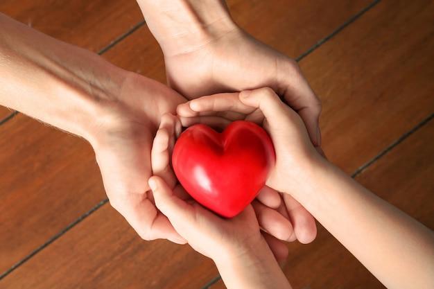 Ręce matki i dziecka z czerwonym sercem na drewnianych