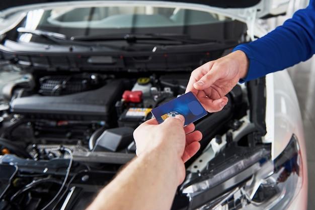 Ręce mechanika samochodowego z kluczem w garażu, płatność kartą kredytową