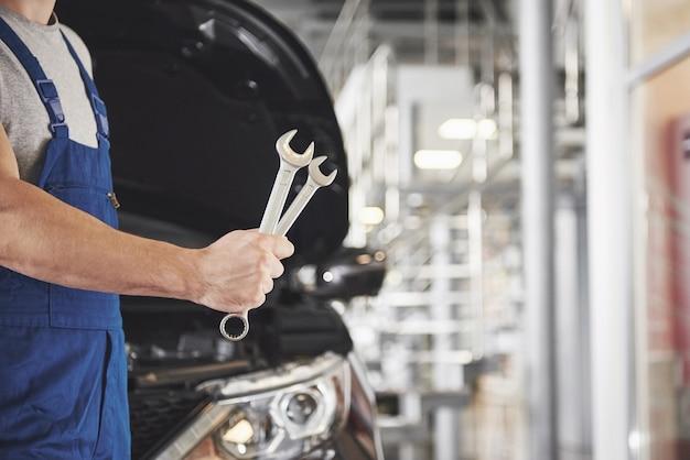 Ręce mechanika samochodowego z kluczem w garażu.