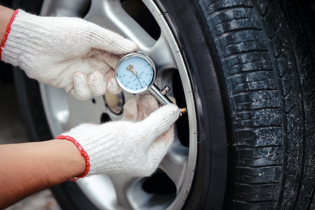 Ręce mechanika sprawdzają ciśnienie powietrza w oponach