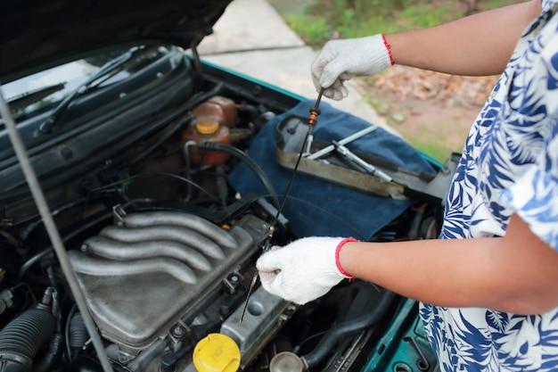 Ręce mechanika sprawdzające poziom oleju