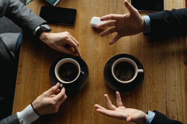 Ręce mężczyzn gestykulują, trzymając filiżanki kawy
