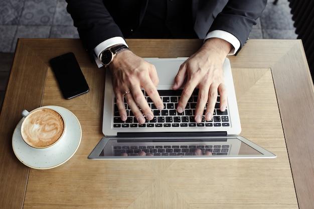 Ręce mężczyzn leżą na laptopie, w pobliżu telefonu i cappuccino