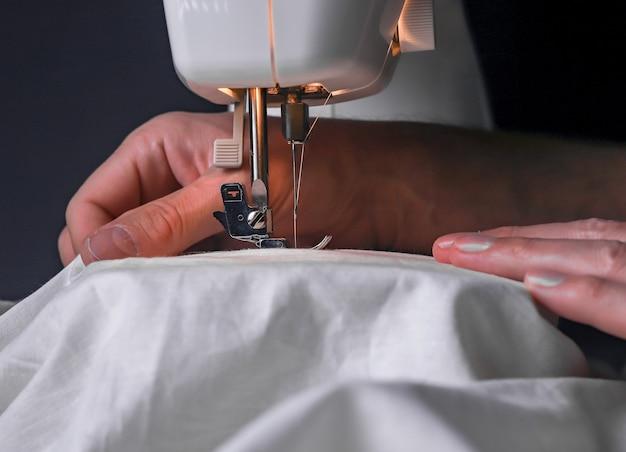 Ręce mężczyzn na maszynie do szycia podczas procesu pracy z bawełnianą szmatką z bliska.