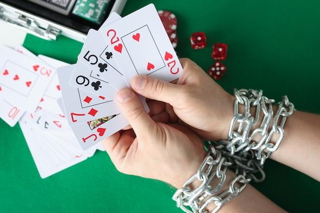 Ręce mężczyzn są związane łańcuchem i trzymają koncepcję uzależnienia od hazardu w karty