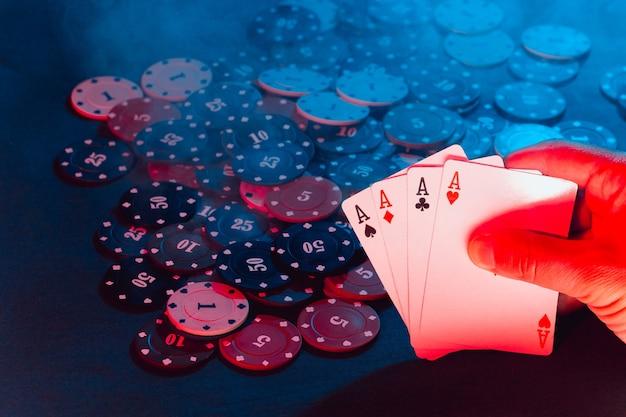 Ręce mężczyzn trzymają karty przy żetonach do gry. na zdjęciu jest dym