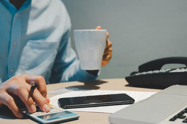 Ręce, mężczyźni trzymają długopis i kalkulator, który działa z telefonami komórkowymi i komputerami. płatności biznesowe online, finanse, inwestycje i podatki.