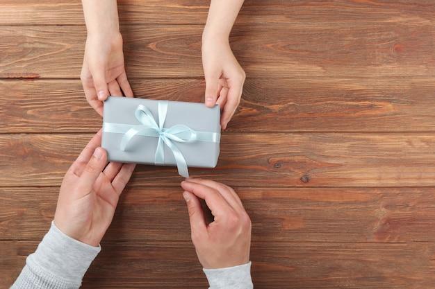 Ręce mężczyzny i dziecka trzymających prezent widok z góry