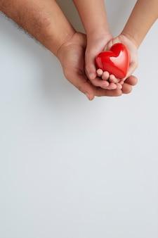 Ręce mężczyzny i dziecka z czerwonym sercem na białej ścianie