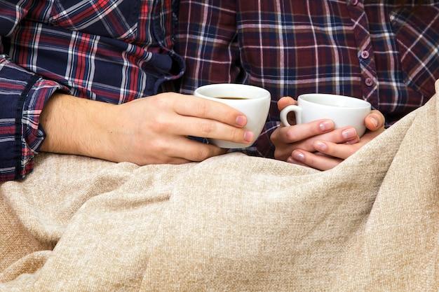 Ręce mężczyzny i kobiety trzymają dwie filiżanki kawy w kratę.