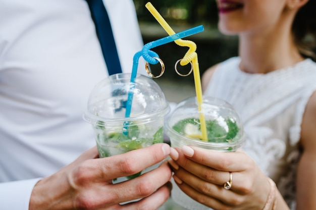 Ręce mężczyzny i kobiety trzymają plastikowe kieliszki wina lub szampana oraz dwie obrączki ślubne