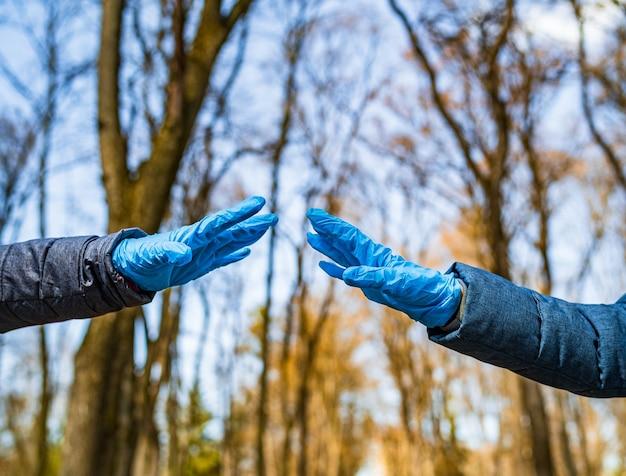 Ręce mężczyzny i kobiety w rękawiczkach medycznych rozciągają się do siebie