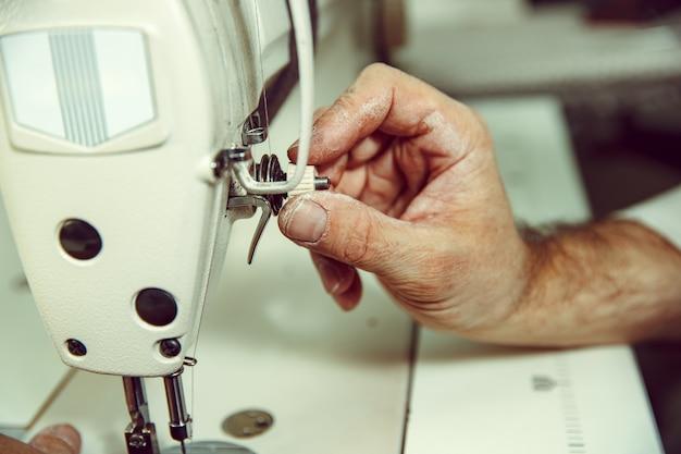 Ręce mężczyzny i maszyna do szycia. warsztat skórzany. tkanina vintage przemysłowa. mężczyzna w kobiecym zawodzie. pojęcie równości płci